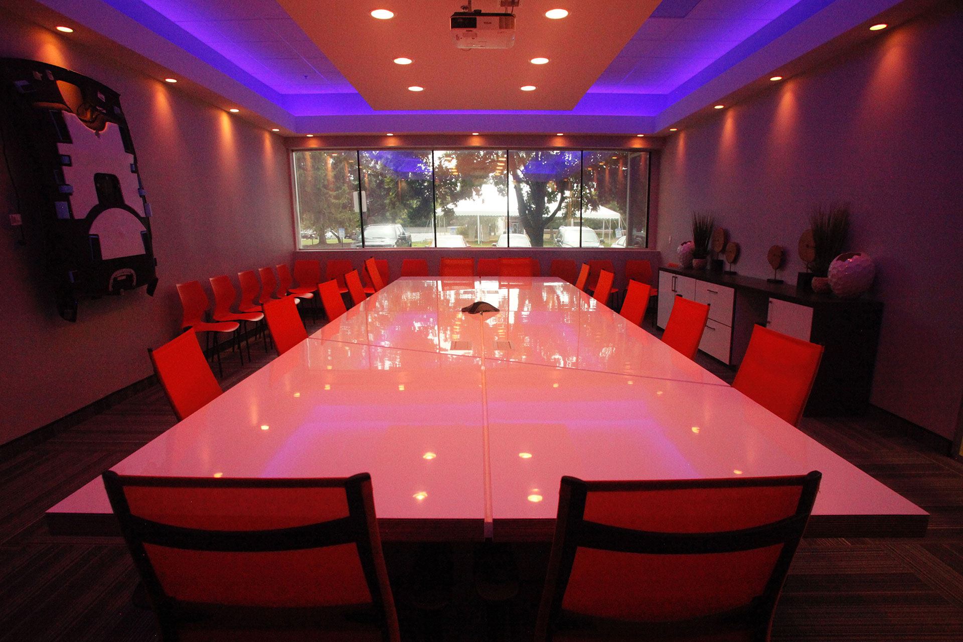 Conference room, custom table with high gloss, Solicore plastic laminate with reveals throughout the table - reflecting their corporate theme in the space. Includes plastic laminate credenza and countertops to match.