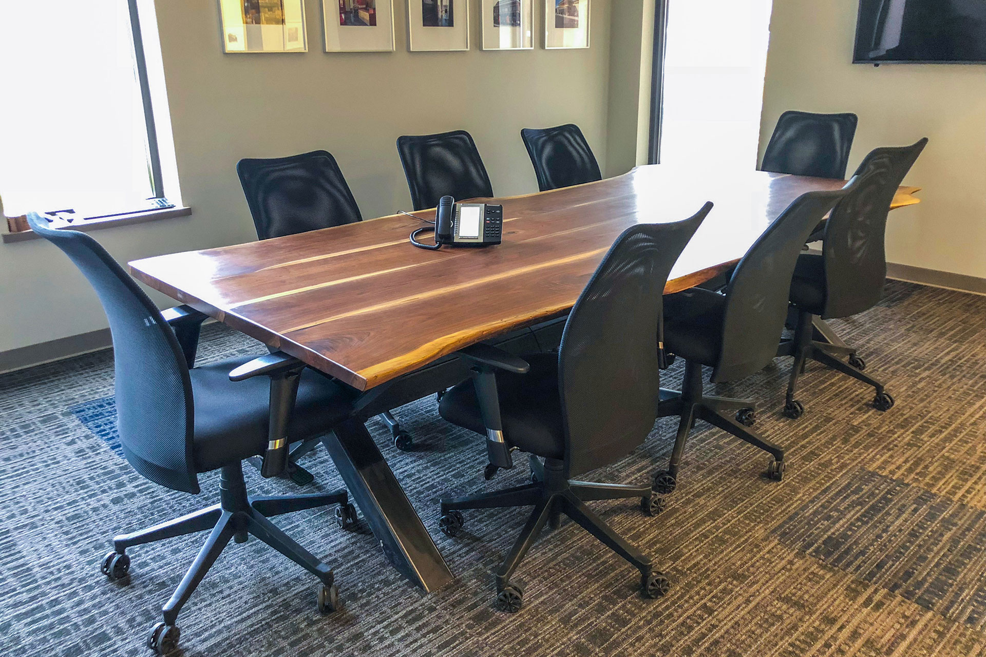 Walnut live-edge custom table top with steel table base for boardroom of corporate office space.
