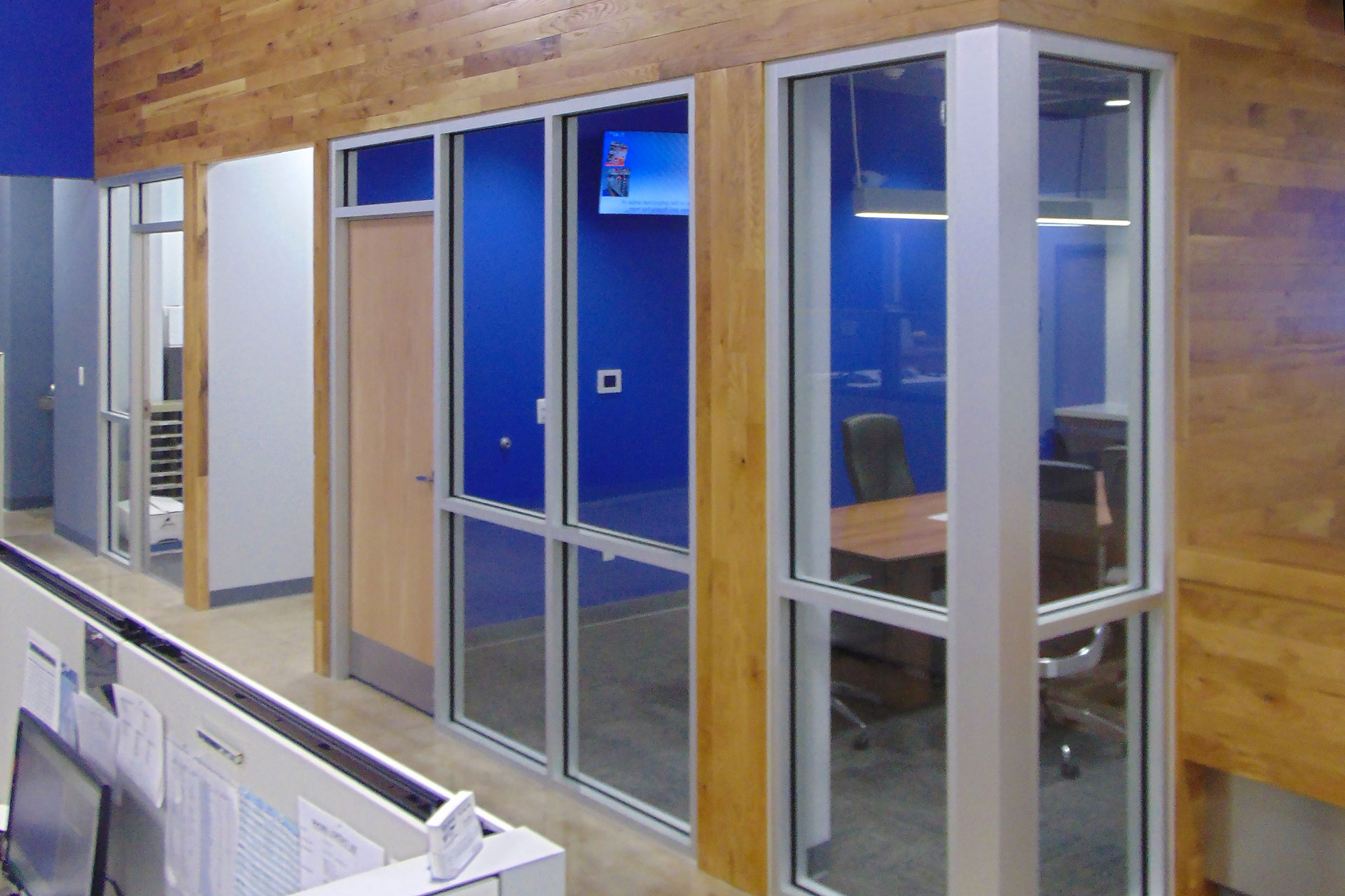 Stained and finished wood planks feature wall installed on existing partition walls.