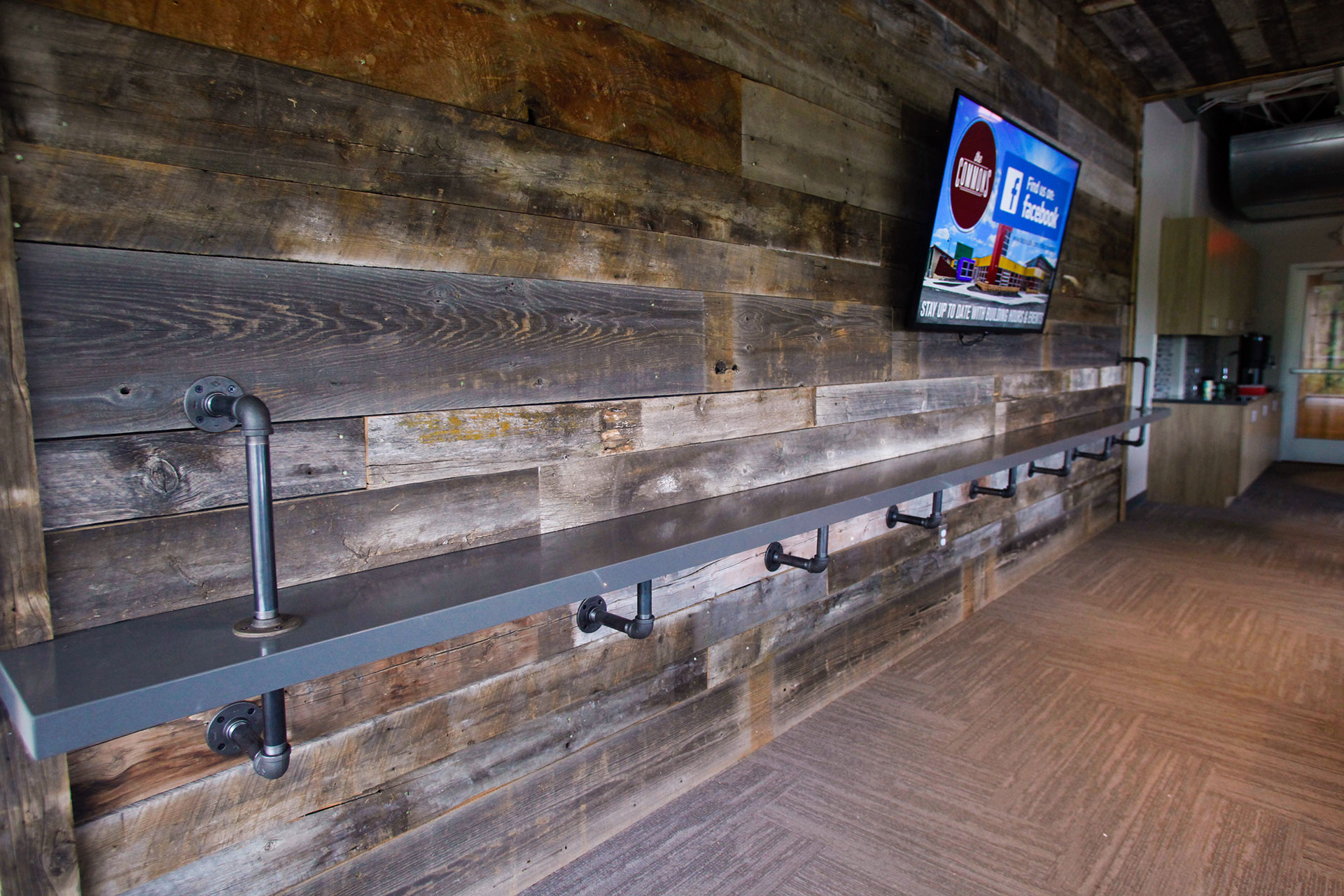 Quartz countertop with blackened pipe supports on reclaimed wood feature wall.