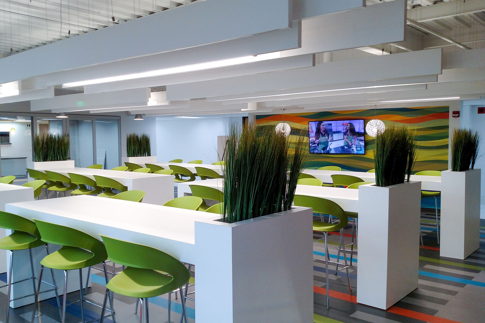 Solicore plastic laminate tables with integrated planters, and custom plastic laminate floating ceiling beams.