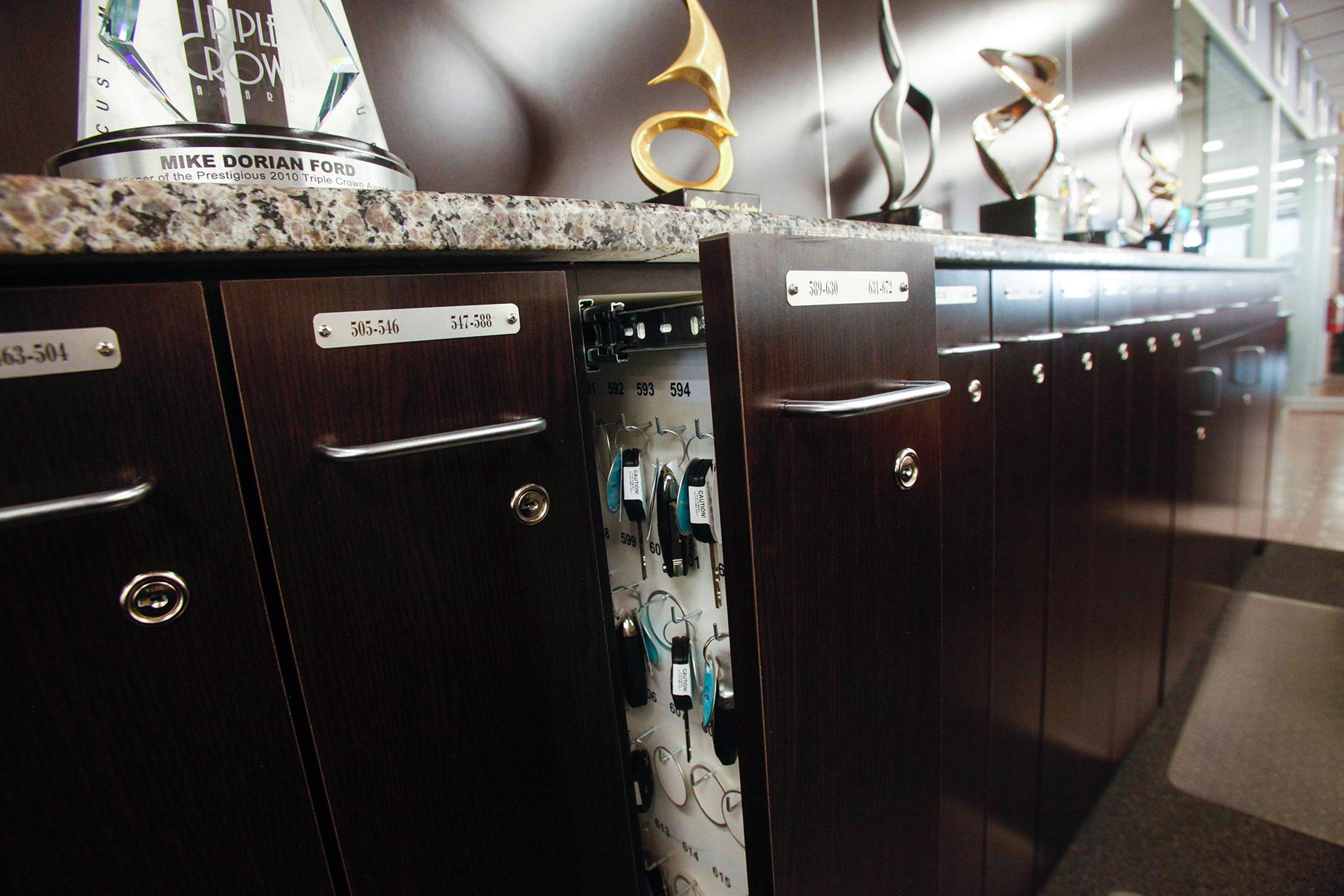 Custom plastic laminate locking key storage cabinets with granite countertop.