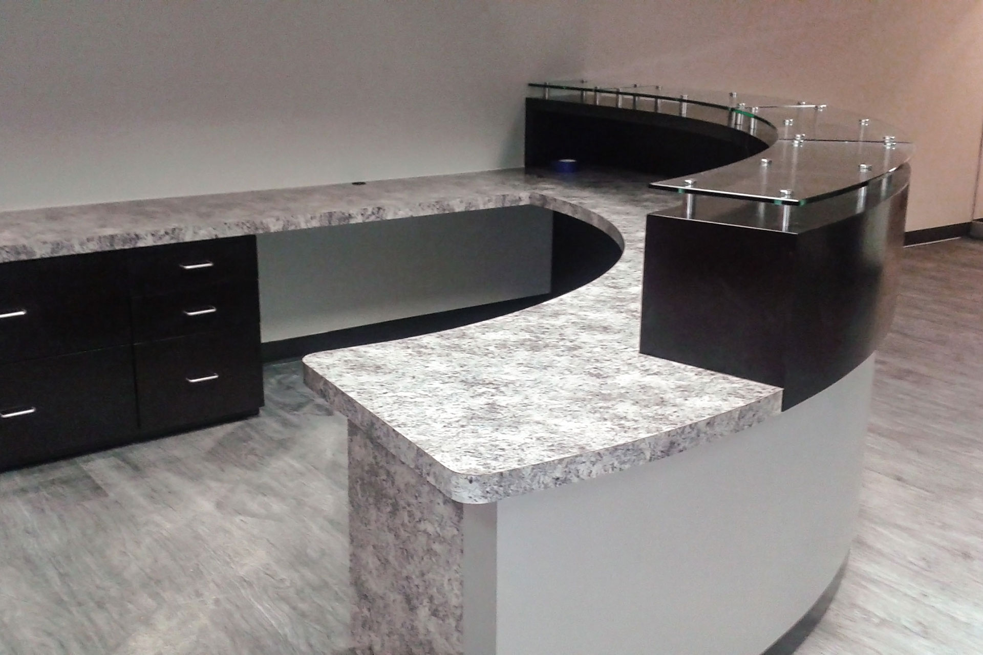 Custom plastic laminate reception desk with plastic laminate cabinets, countertop and transaction top with glass-on standoffs.