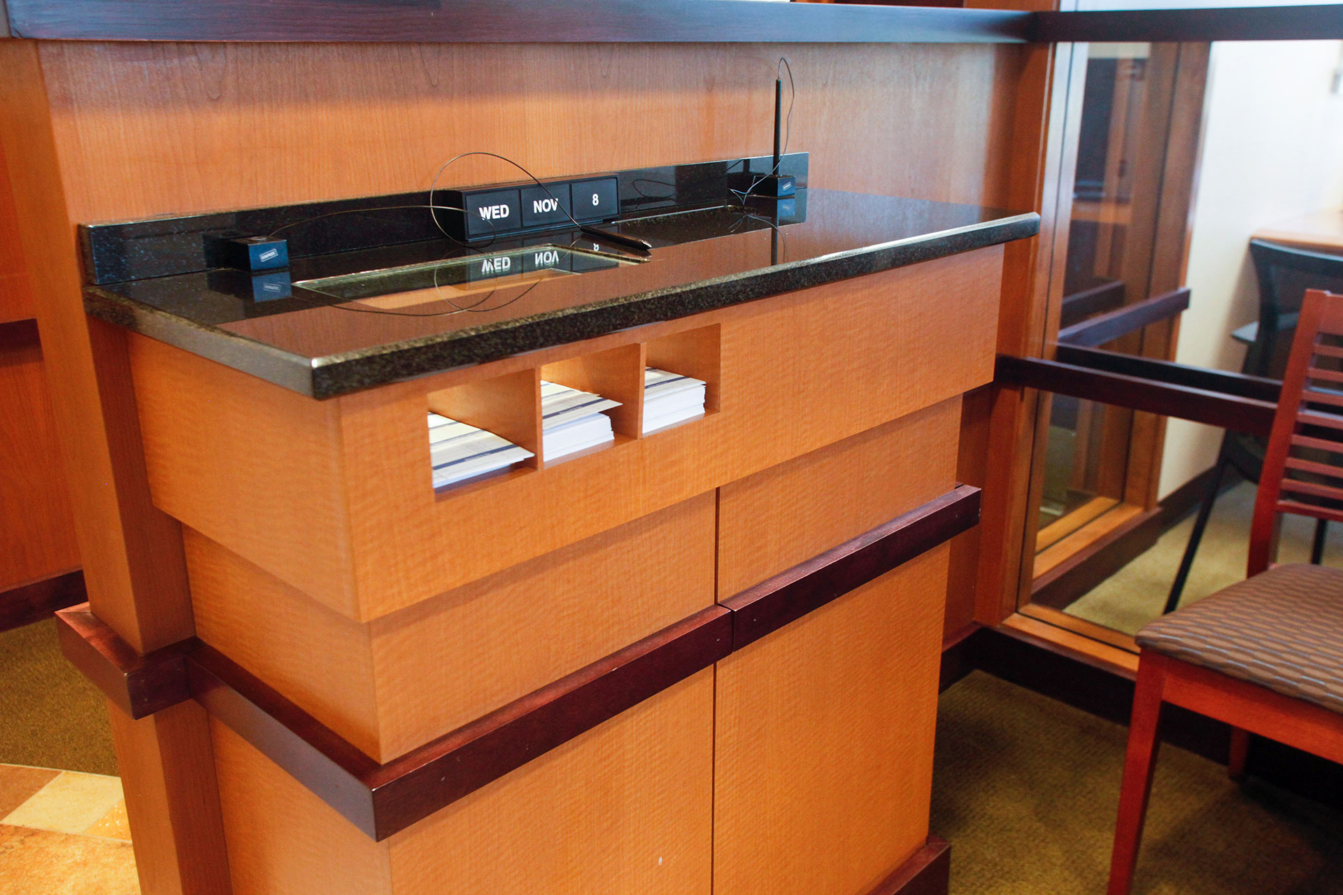 Custom plastic laminate check writing station with granite countertop and stained and finished wood trim.