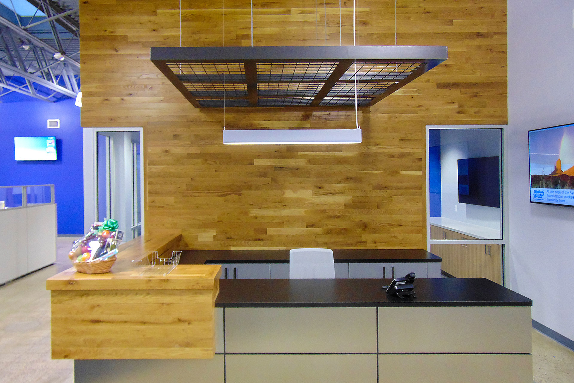 Reception desk with plastic laminate partial-height wall with reveals, and plastic laminate cabinets and counter top, and stained and finished wood transaction top to match the wood/slat feature wall. Fabricated and installed the metal hanging ceiling feature piece.