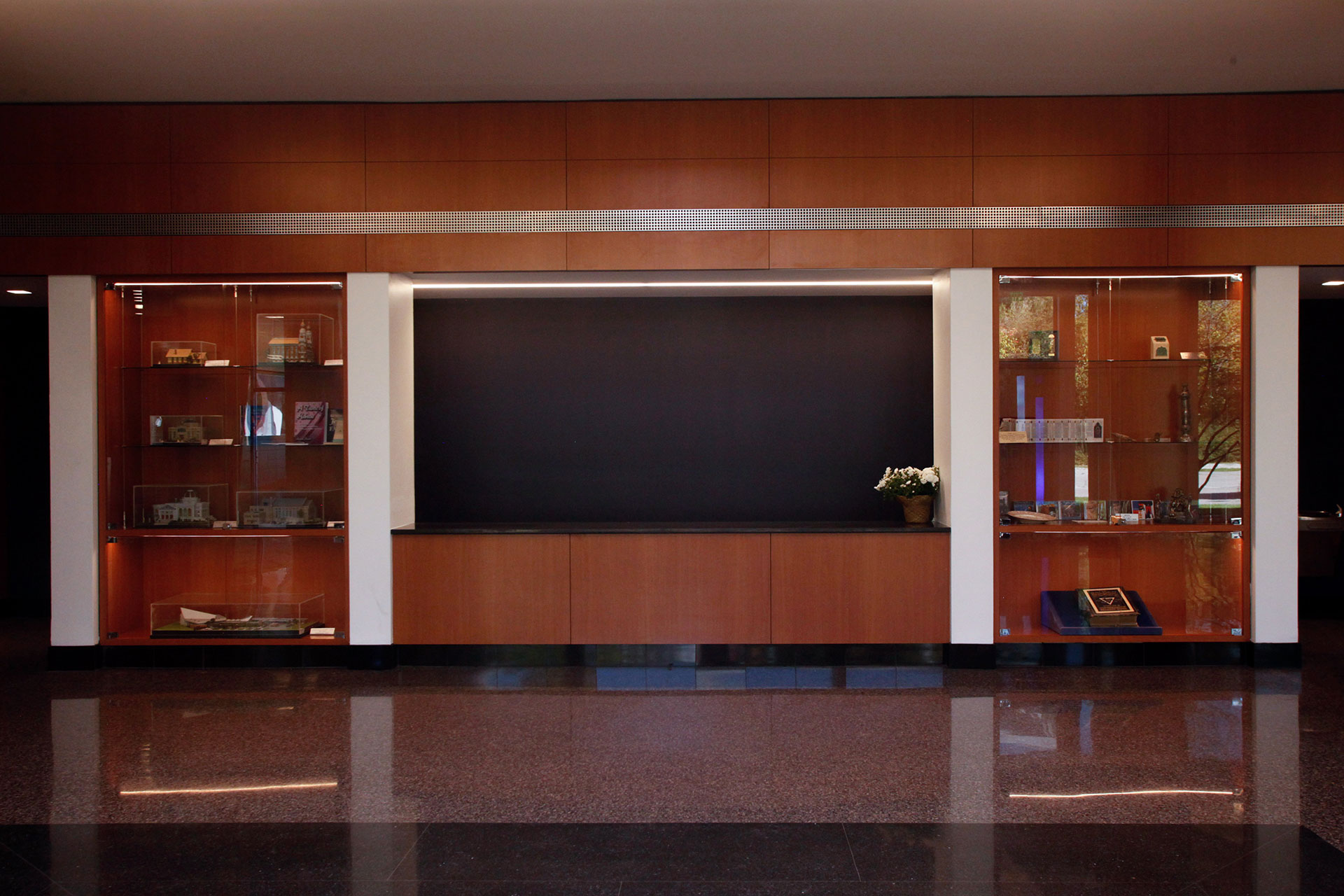 Plastic laminate wall panels with reveals and integrated cabinets with glass doors.