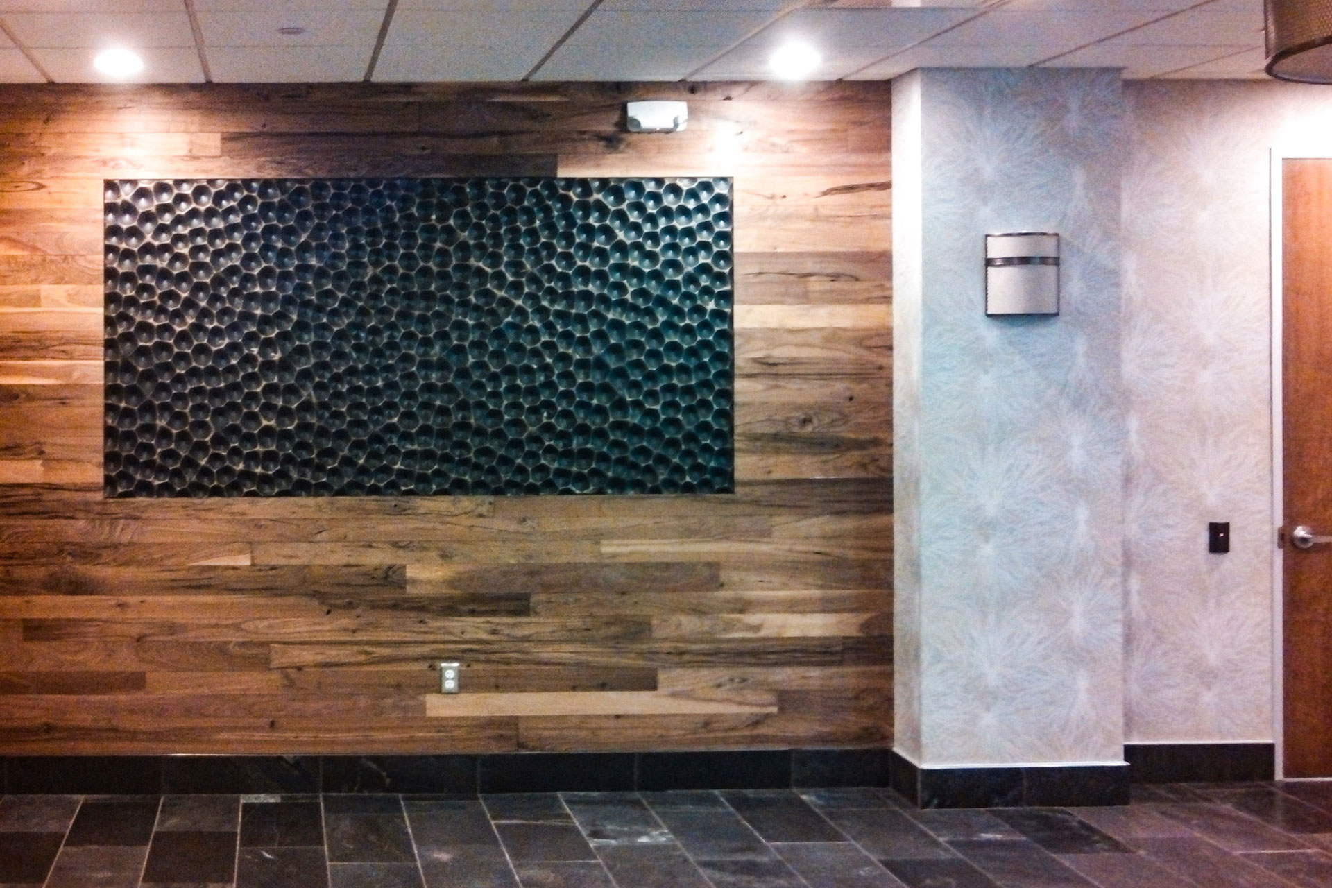 Walnut slat wall with inset painted and textured panel.