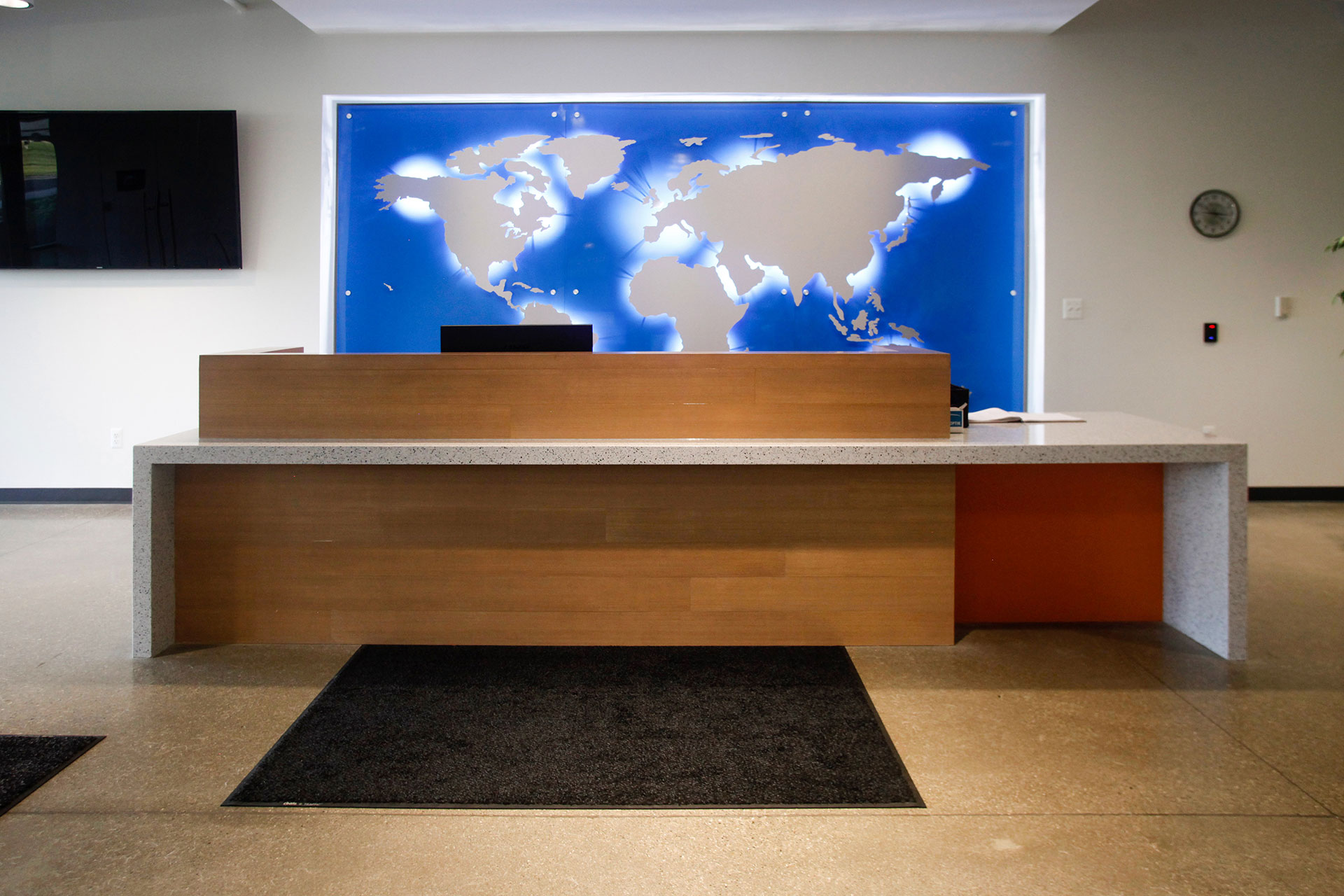 Reception desk with quartz countertop and waterfall end panels, with stained and finished wood veneer panel and transaction top.