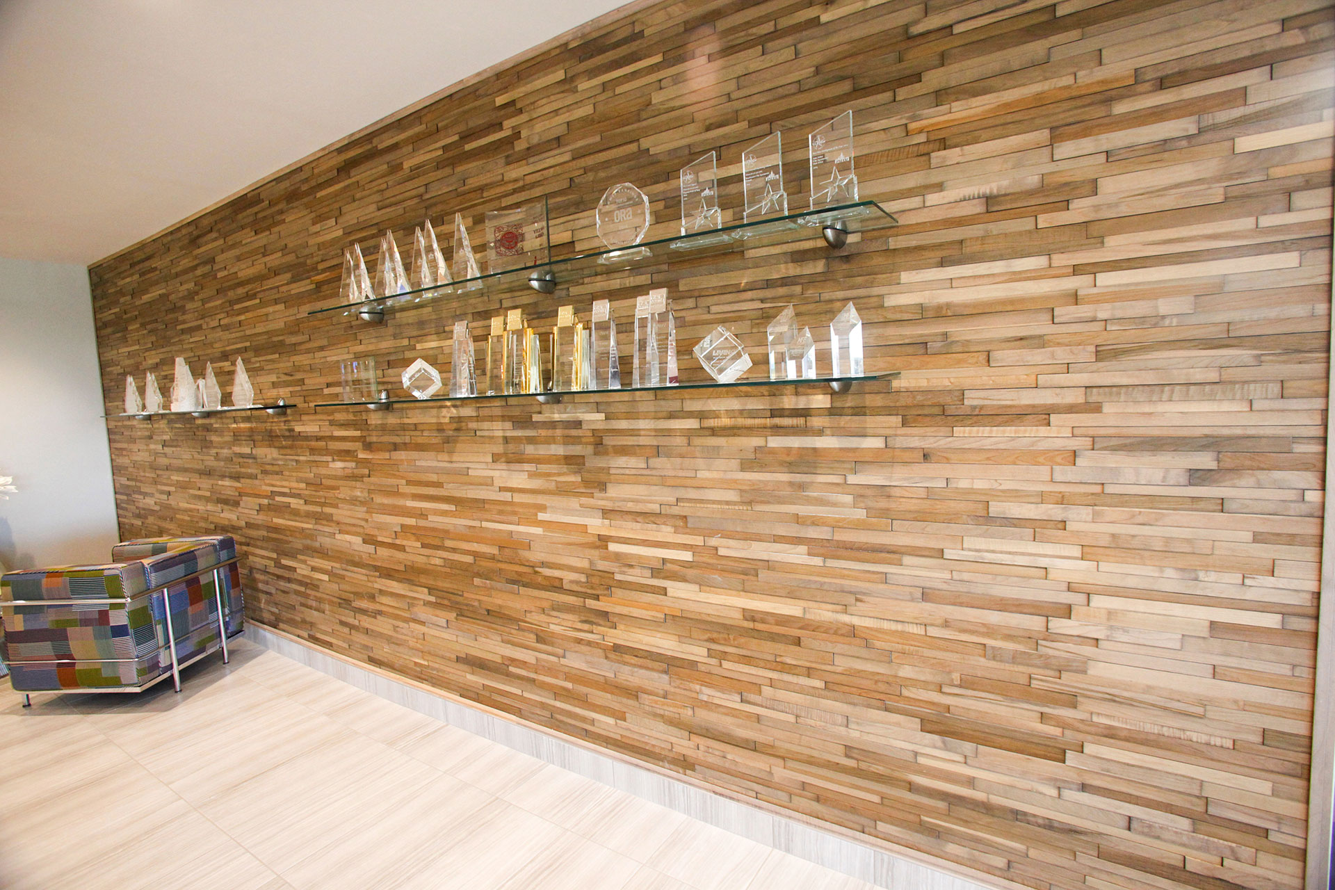 Custom wood feature wall with glass shelving.