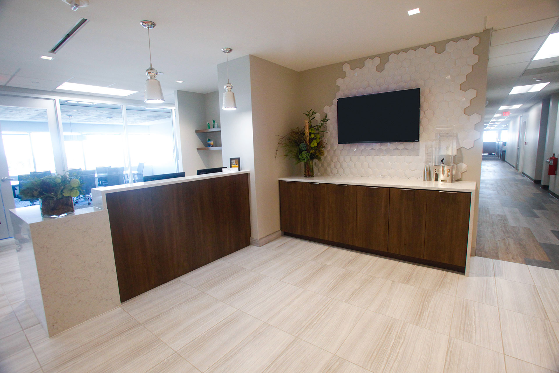 Reception desk with quartz tops and panels, and recessed plastic laminate panel. Also plastic laminate cabinets with quartz countertop and end panel.