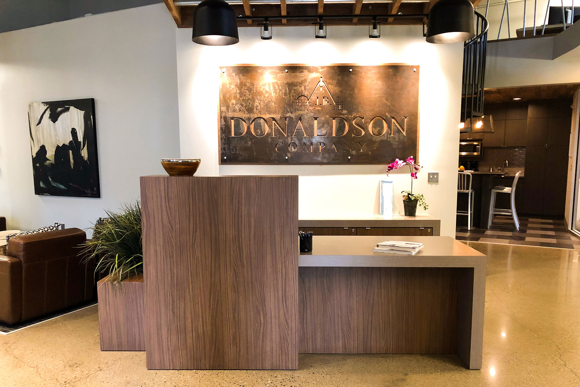 Custom reception desk with plastic laminate cabinets and countertops with matching plastic laminate planter box, and suspended rough-sawn walnut trellis above, and plastic laminate/steel sign.