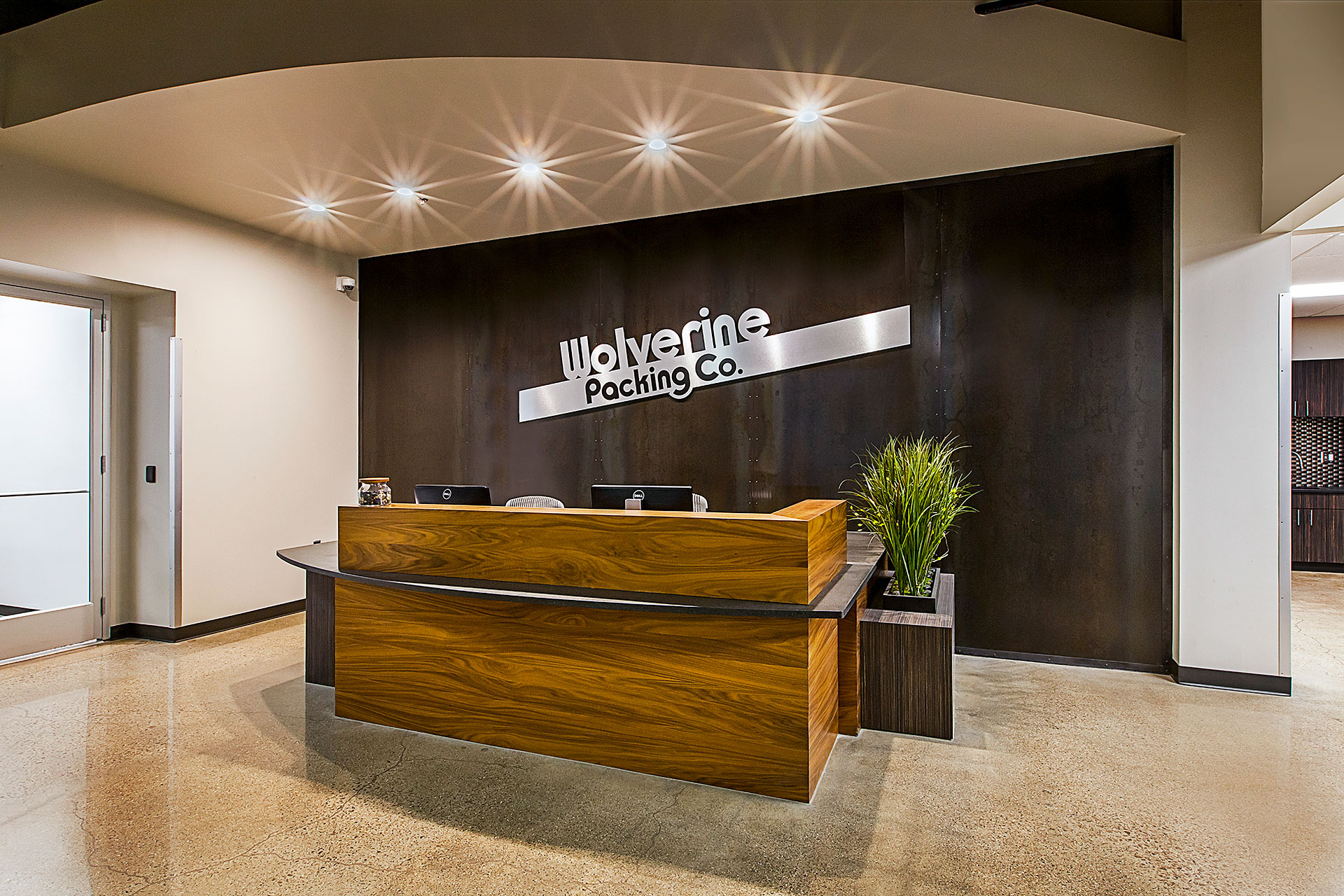 Custom reception desk with walnut veneer slats, granite countertop and plastic laminate planter box with treated and sealed steel wall panels behind.