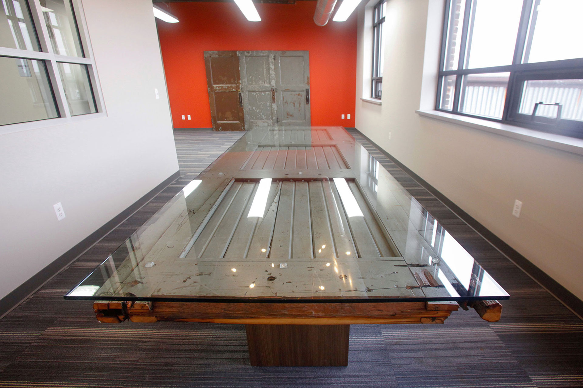Reclaimed wood door re-purposed as a custom conference table with plastic laminate support bases and glass top.