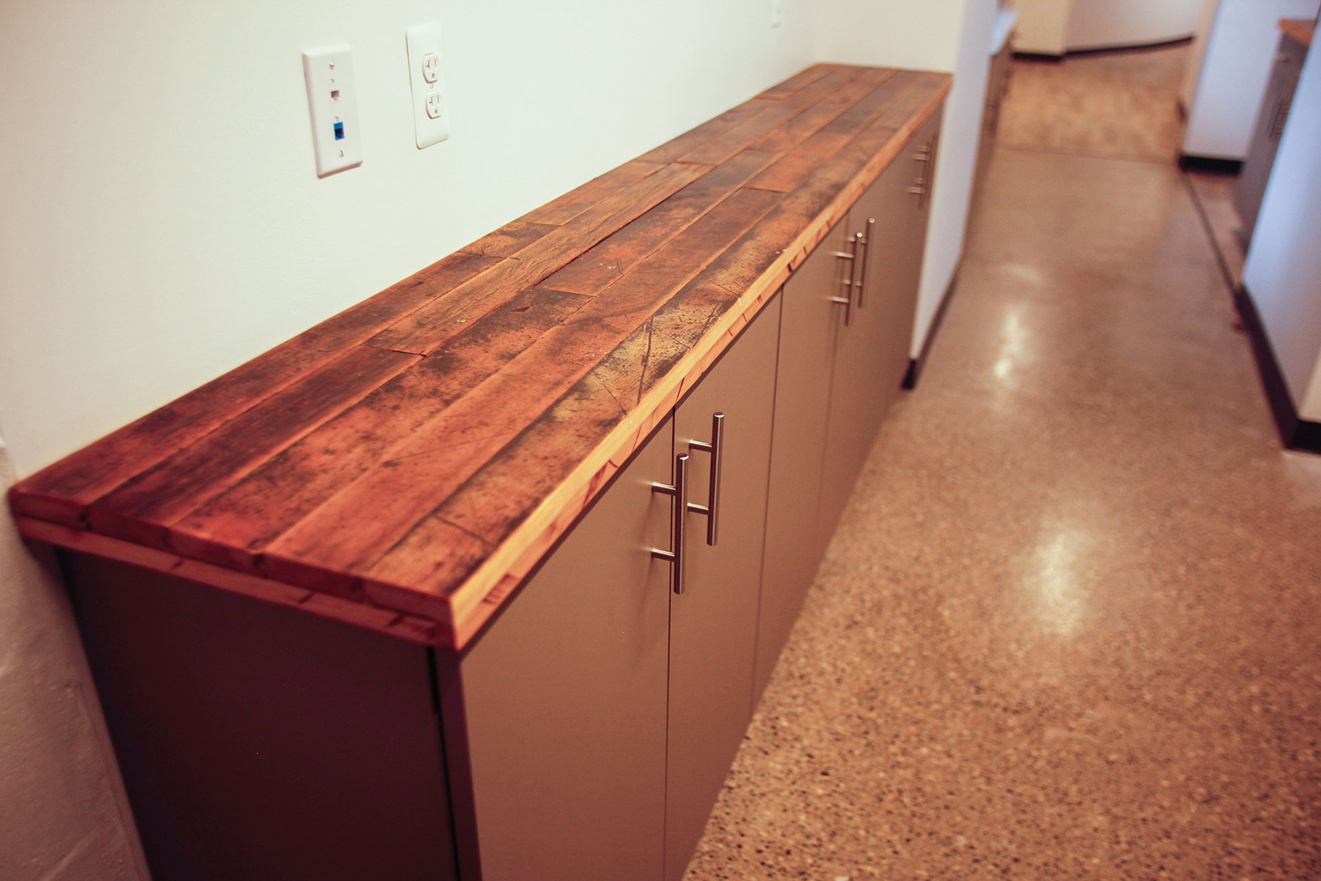 Plastic laminate base cabinets with reclaimed wood flooring countertops.